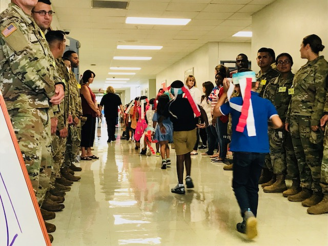 Students wearing patriotic colors walking in hallway with soldiers and teachers